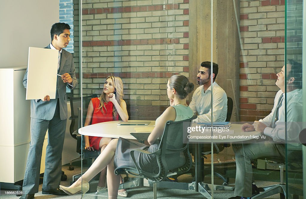 Man presenting to business people in office