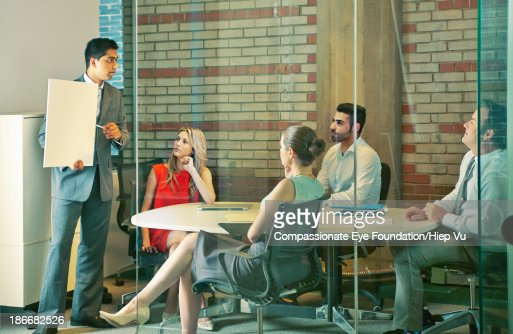 Man presenting to business people in office : Stock Photo