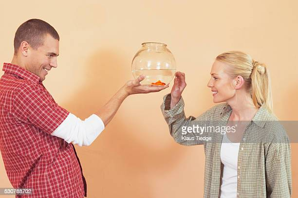 Man presenting woman with gold fish in bowl