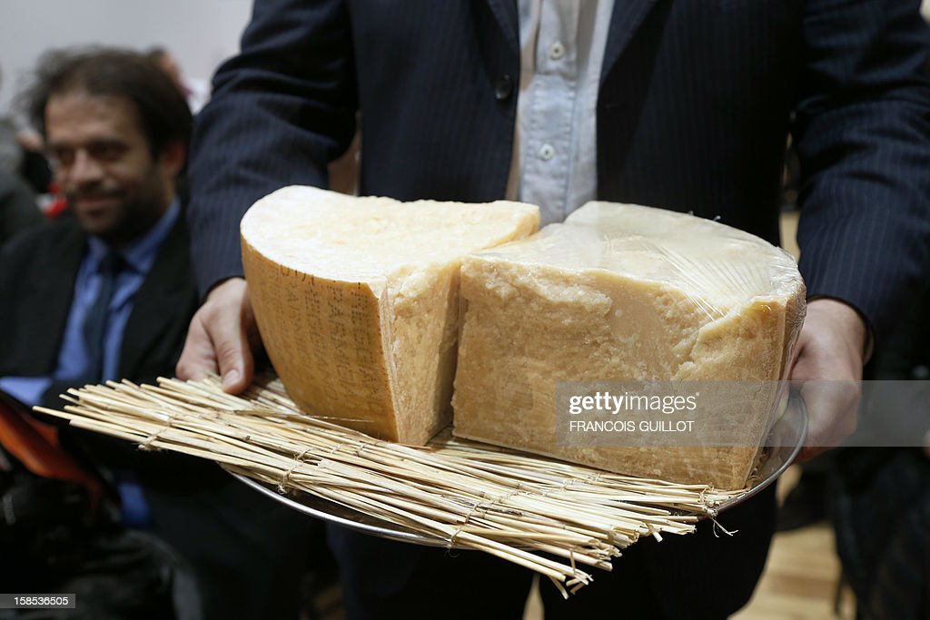 A man presents pieces of Parmigiano Reggiano during a sale of fine food to raise funds for the French Red Cross on December 18 2012 French auction...