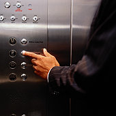 Man Pressing a Button in an Elevator