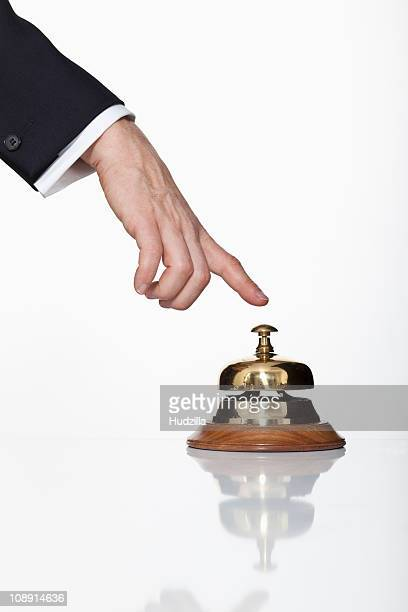 A man pressing a service bell, focus on hand