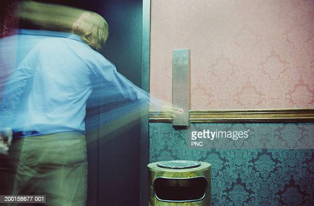 Man pressing elevator push button, rear view (blurred motion)