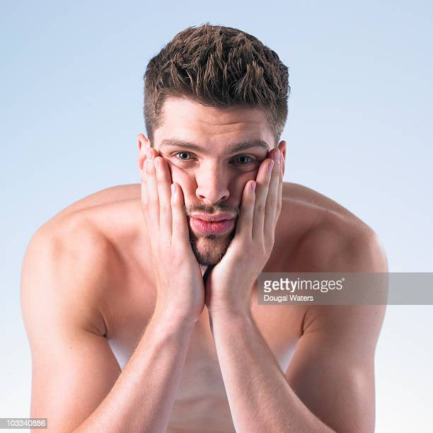 Man pressing hands against face.