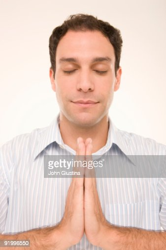 Man pressing palms together, eyes closed. : Stock Photo
