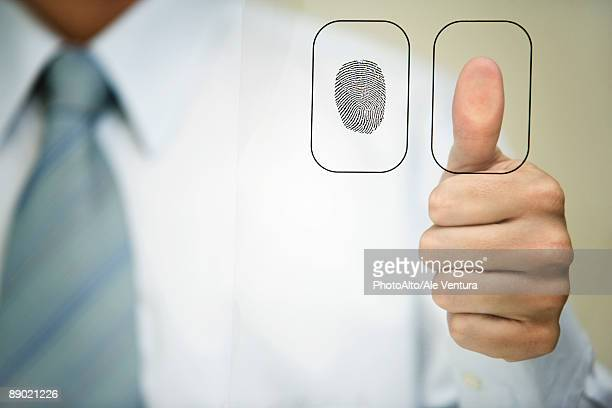 Man pressing thumb to fingerprint reader