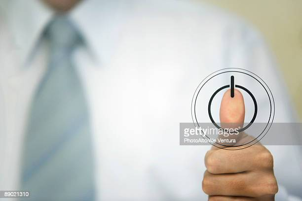 Man pressing thumb to power button