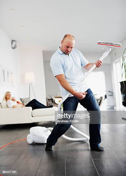 A man pretending the vacuum cleaner to be a guitar Sweden.