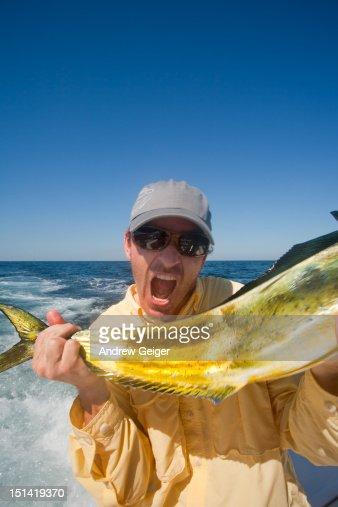 Man pretending to eat whole Dorado fish. : Stock Photo