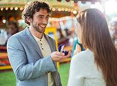 Man proposing to girlfriend in amusement park