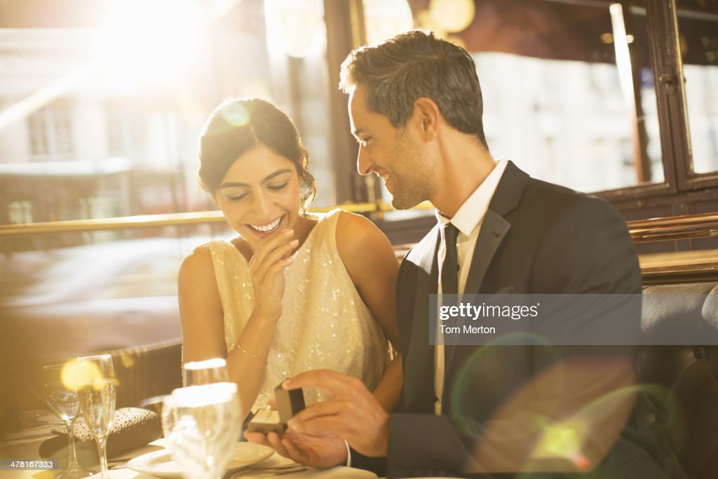 Man proposing to girlfriend in restaurant