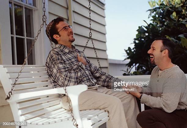 Man proposing to man on patio