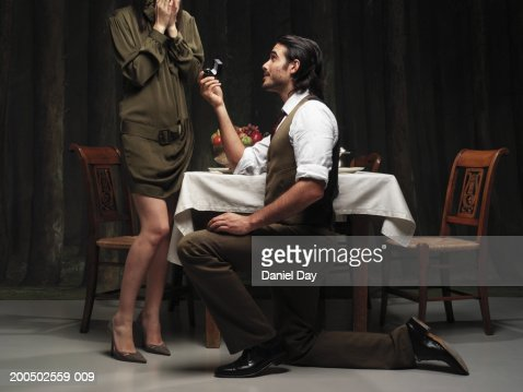 Man proposing to woman at dinner table