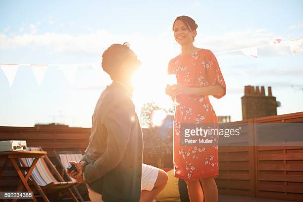 Man proposing to woman on roof terrace, sunset in background