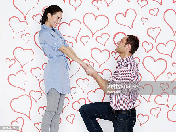 Man proposing to woman surrounded by love hearts