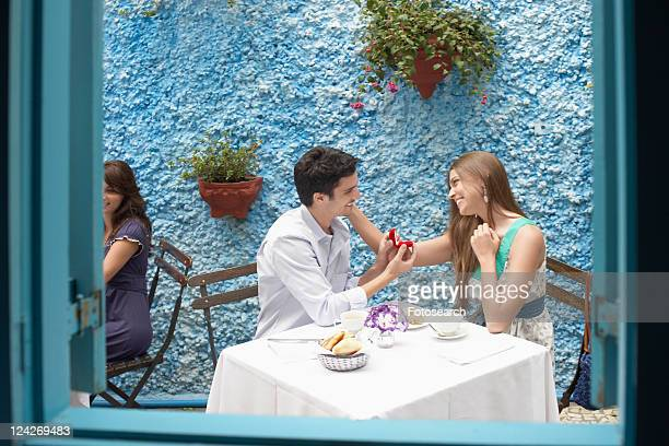 Man proposing woman in restaurant, woman touching his face