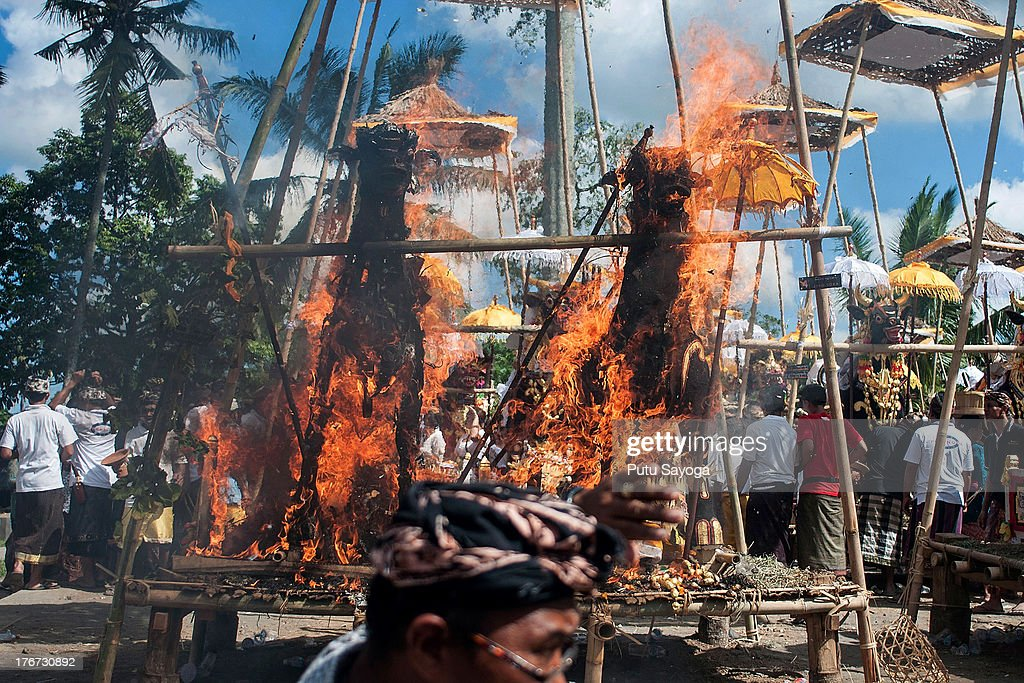 A man protects himself from the heat as sarcophagi burn at the cremation site during a Balinese Hindu mass cremation on August 18, 2013 in Ubud, Bali, Indonesia. More than 60 corpses were collectively cremated to share the expense of the ceremony. Well known as Ngaben, it is one of the most important ceremonies for Balinese Hindu people, as they believe it will free the spirit from the deceased body so it can reincarnate.