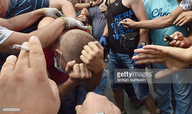 A man protects his face as residents of Kiev clash with 'Maidan' activists on August 9 2014 as hundreds of local volunteers backed up by municipal...