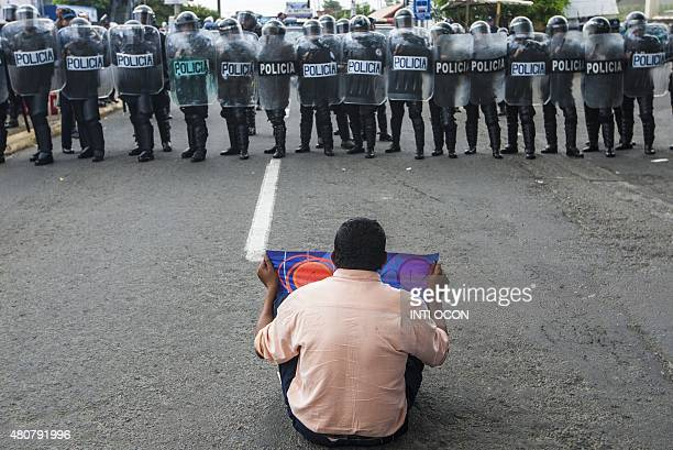 A man protests against the electoral system in front of a line of riot policemen in Managua Nicaragua on July 15 2015 AFP PHOTO / Inti OCON