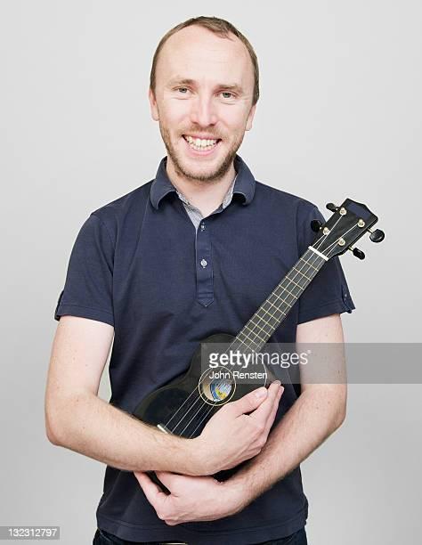 man proudly holding ukulele