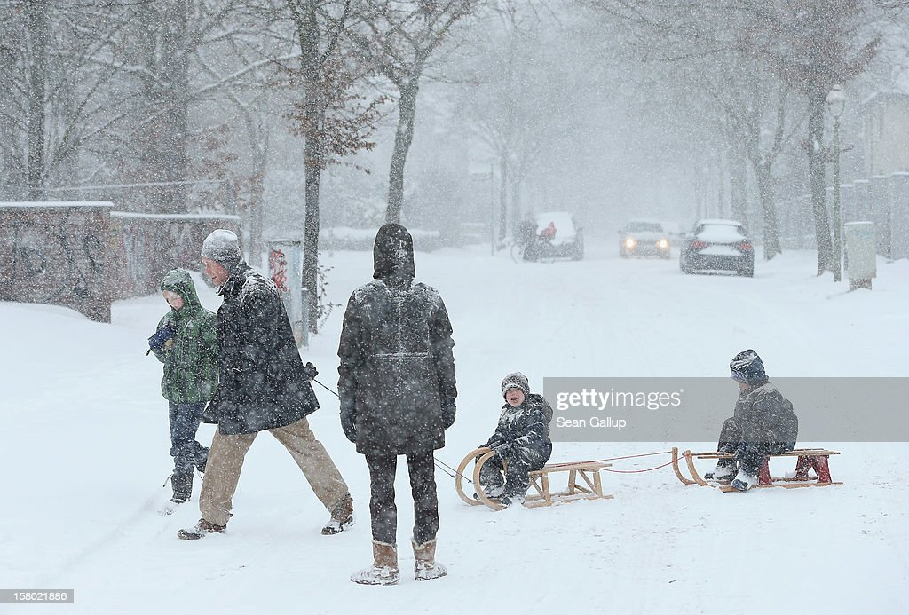 A man pull children on sleds across a snow-covered street during a heavy snowfall in Zehlendorf district on December 9, 2012 in Berlin, Germany. Northeastern Germany was inundated with snow that covered highways and blanketed the region.