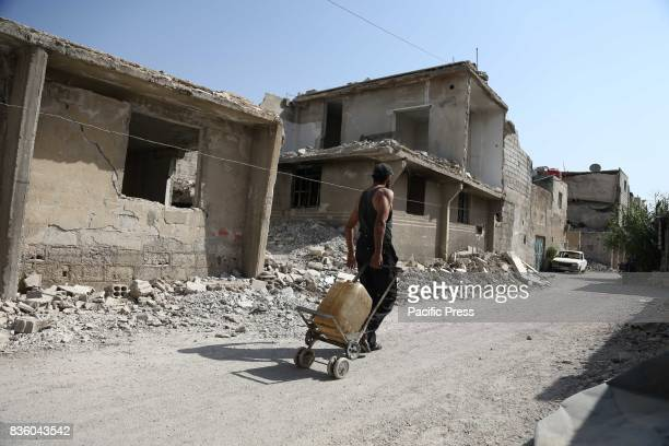 A man pulling a cart containing a vase of water on a destroyed road in Zamalka in the East Ghouta and This area is controlled by the Syrian opposition