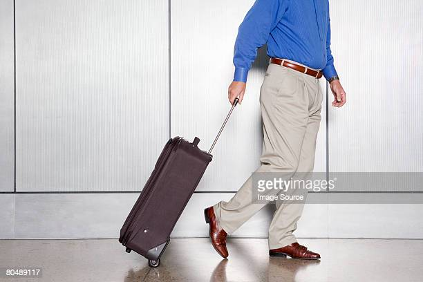 A man pulling a suitcase along