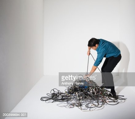 Man pulling cable from pile of cables : Stock Photo
