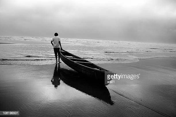 Man Pulling Canoe Boat Off Beach into Water