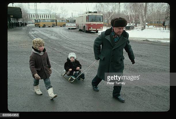 Man Pulling Children on a Sled