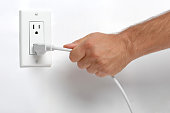 Man Pulling Electrical Plug from Wall Socket on Whte