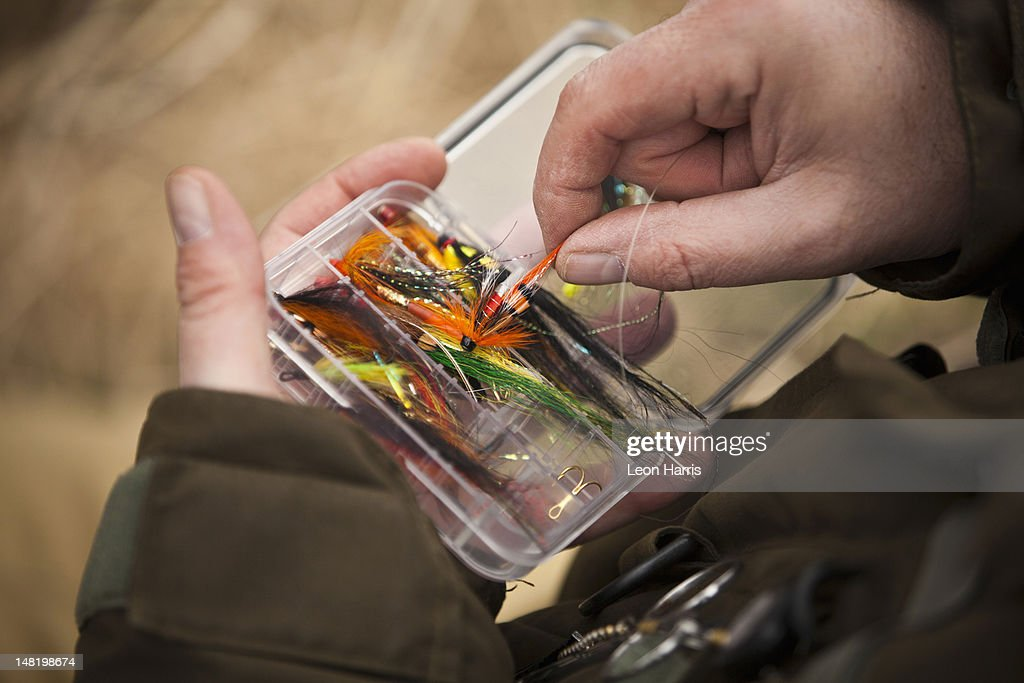 Man pulling fishing tackle from box