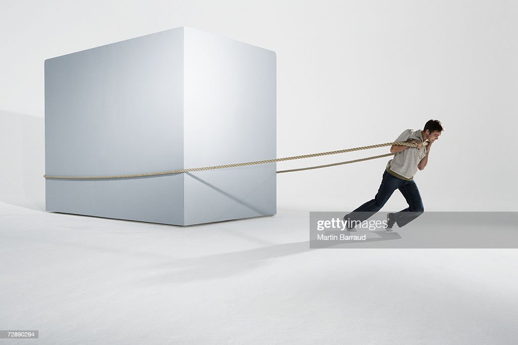 Man pulling giant box with rope : Stock Photo