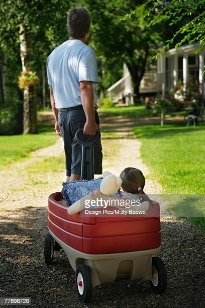 Man pulling girl in red wagon