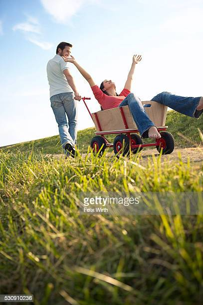 Man pulling his girlfriend in a wagon