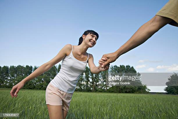 A man pulling his girlfriend through a field