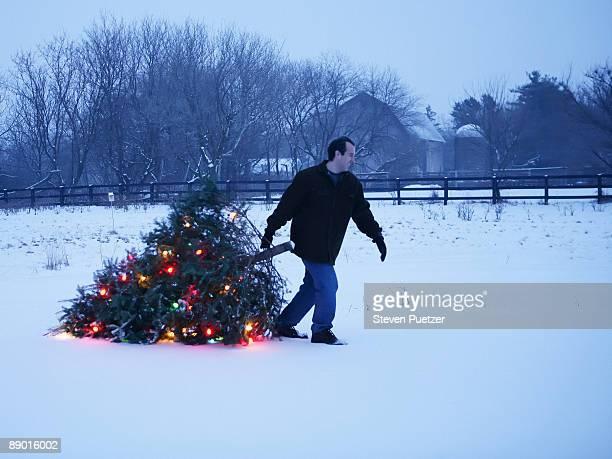 Man pulling illuminated Christmas tree in snow
