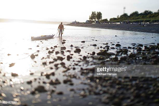Man pulling kayak towards beach