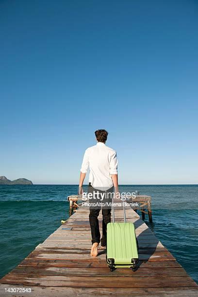 Man pulling luggage walking towards end of pier, rear view