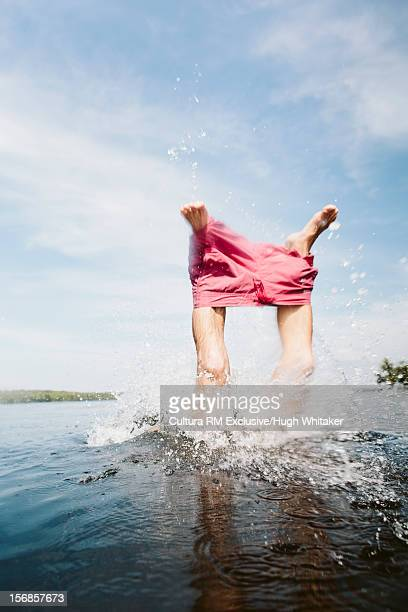 Man pulling off shorts in lake