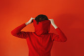 Man pulling red sweater over face against red background