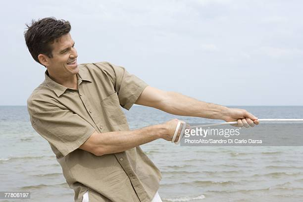 Man pulling rope, smiling, ocean in background, waist up