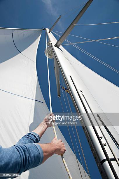 Man pulling ropes on yacht