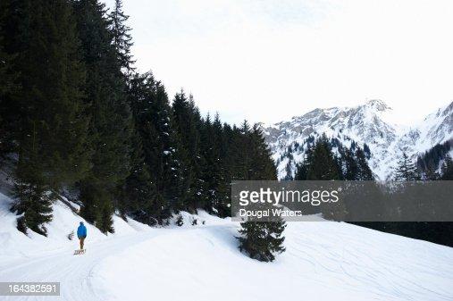 Man pulling sledge in Swiss Alps landscape
