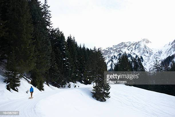 Man pulling sledge in Swiss Alps landscape