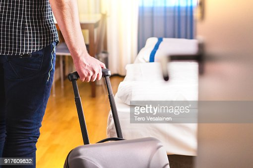 Man pulling suitcase and entering hotel room. Traveler going in to room or walking inside motel with luggage. : Stock Photo