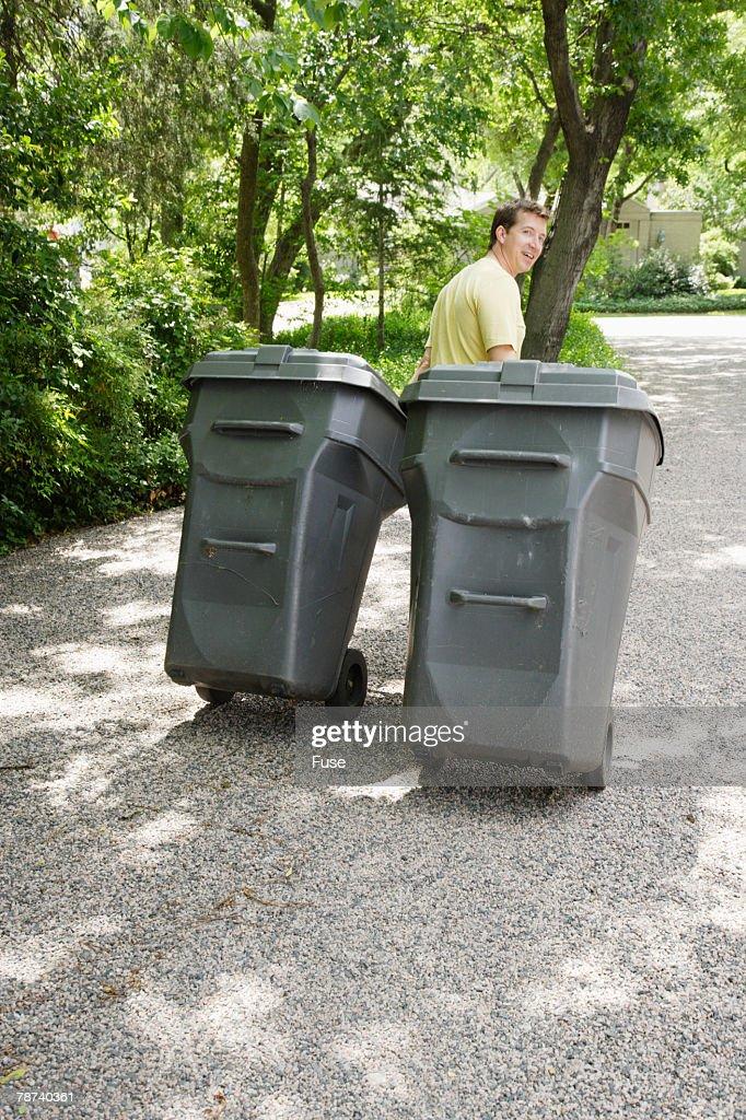 man pulling trash bins on driveway stock photo