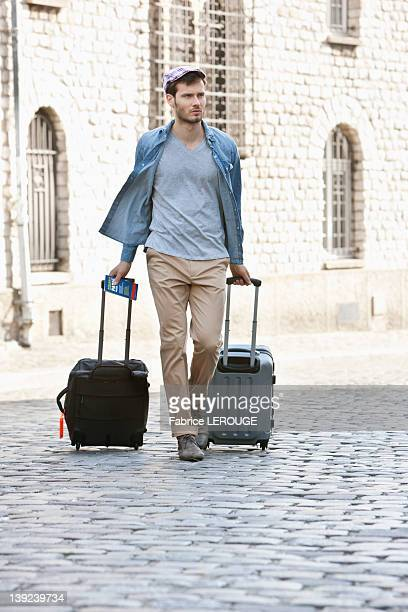 Man pulling trolley bags on the road, Paris, Ile-de-France, France