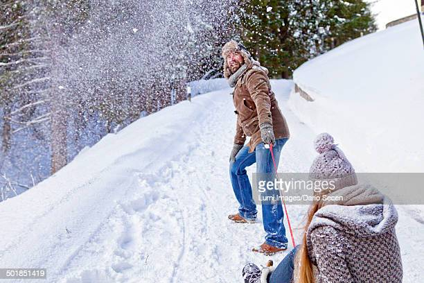 Man Pulling Woman On Sled, Spitzingsee, Bavaria, Germany, Europe
