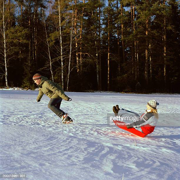 Man pulling woman on sledge on frozen lake by forest, winter